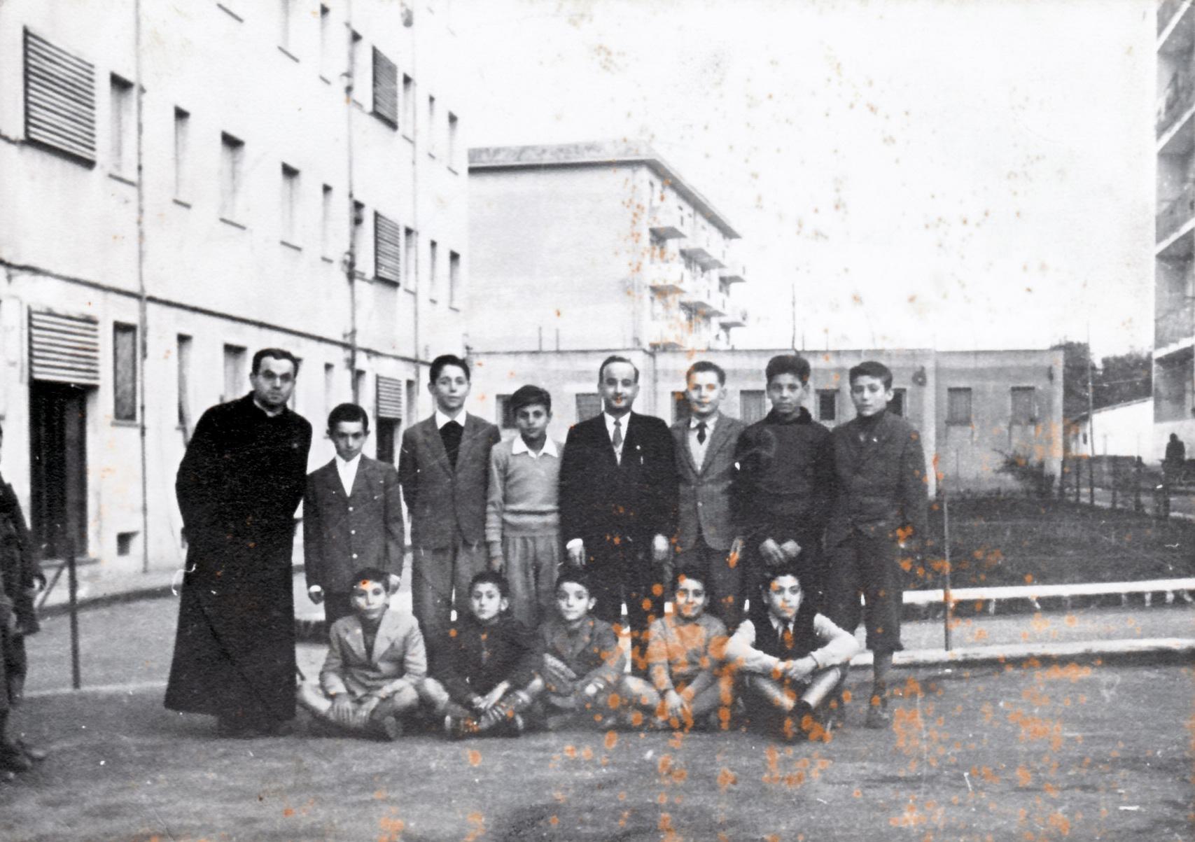 """""""Anno 1956: albori del coro 'Pueri Cantores'. Il sacerdote è l'indimenticato e indimenticabile don Ciro Donnarumma; il maestro è il prof. Antonio Gentile fattosi anche lui prete successivamente. Io sono al centro dei 5 seduti per terra (faceva un freddo cane). La circostanza è uno dei giorni della novena mattutina all'IMMACOLATA subito dopo la S.Messa. Naturalmente, siamo al Rione S. Marco e la """"chiesa"""" era ubicata nello scantinato della palazzina che si vede a sinistra. Il custode era don Antonio (non ricordo più il cognome) ed era colui che dava la voce 'Fratielle e surelle'. Provo a ricordare i nomi scusandomi con gli interessati se salto qualcuno: (da sinistra in alto) don Ciro,Gennaro Ricci, mio fratello Antonio, Antonio Amato, il M° Gentile, ? Esposito. Carlo Salerno,Vincenzo Casulli; (seduti da sinistra): ? ?, Raffaele Giordano, io, Antonio Guarracino, ? ?. Saluti a tutti i liberoricercatori"""". Remigio Russo."""